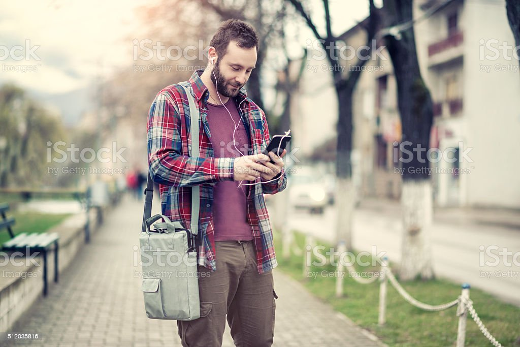 Young and handsome male listening music on mobile smart phone at...