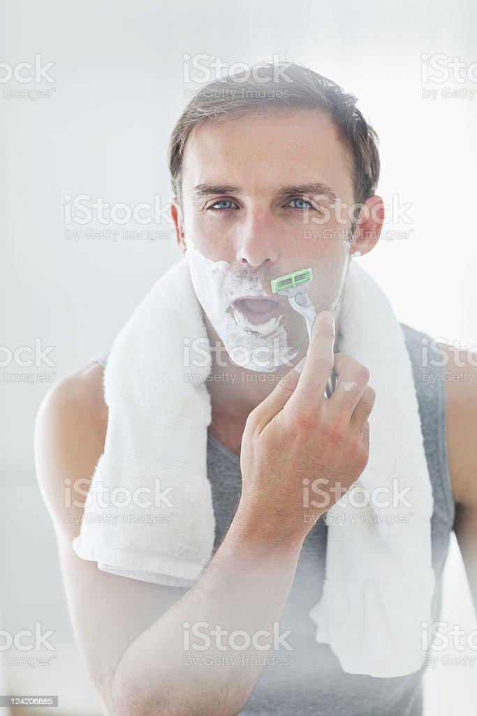 Handsome man looking at camera shaving royalty-free stock photo