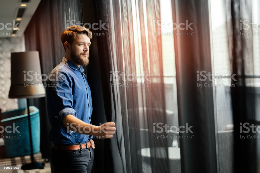 Handsome man looking at cityscape through skyscraper window stock photo