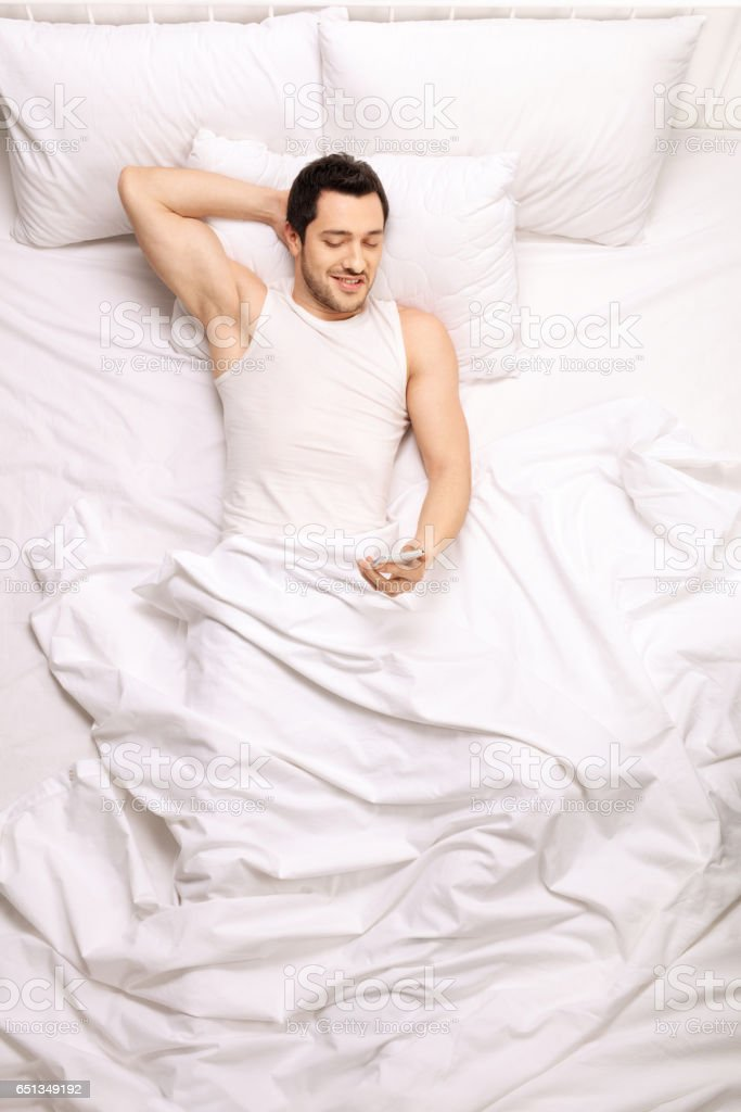 Handsome man looking at a mobile phone while lying in bed