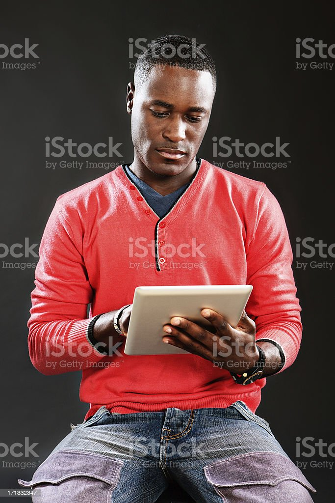 Handsome man looks down, concentrating on digital tablet touch screen stock photo