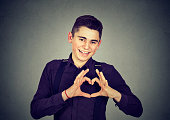Handsome man makes heart shape with fingers hands