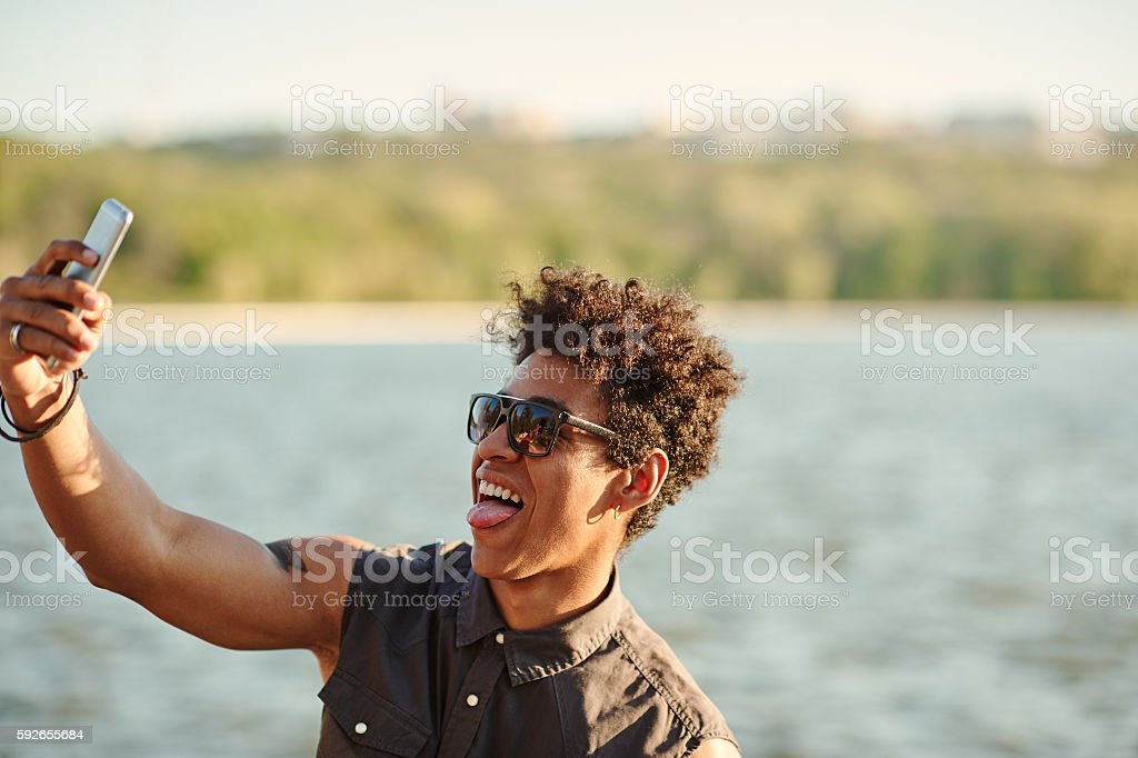 Handsome man making selfie and grimacing with opened mouth stock photo