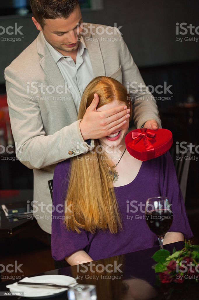 Handsome man offering present to his girlfriend royalty-free stock photo