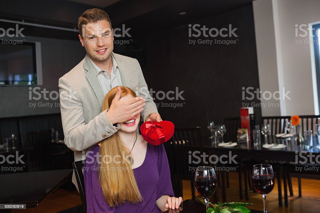 Handsome man offering present to his pretty girlfriend royalty-free stock photo