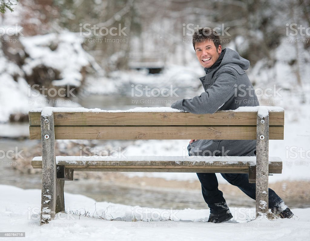 Handsome Man on a Bench in the Snow stock photo