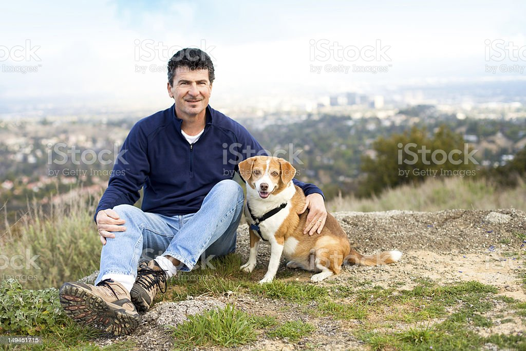 Handsome Man on a Hill Top with his Dog royalty-free stock photo