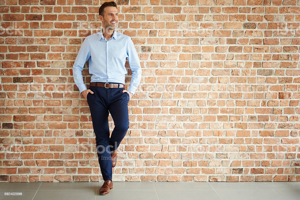 Handsome man on brick wall stock photo