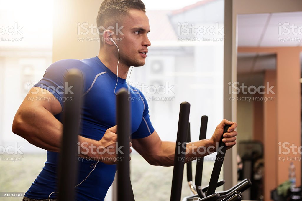 Handsome man on elliptical trainer stock photo