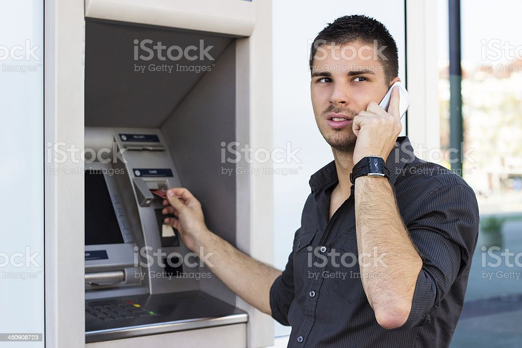 Handsome man on the phone at ATM royalty-free stock photo