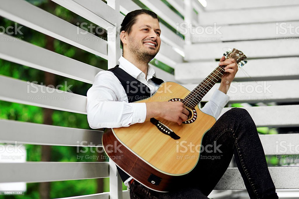 Handsome man playing guitar on the stairs. Attractive male smiling stock photo