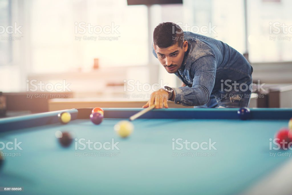 Handsome man playing pool in pub stock photo
