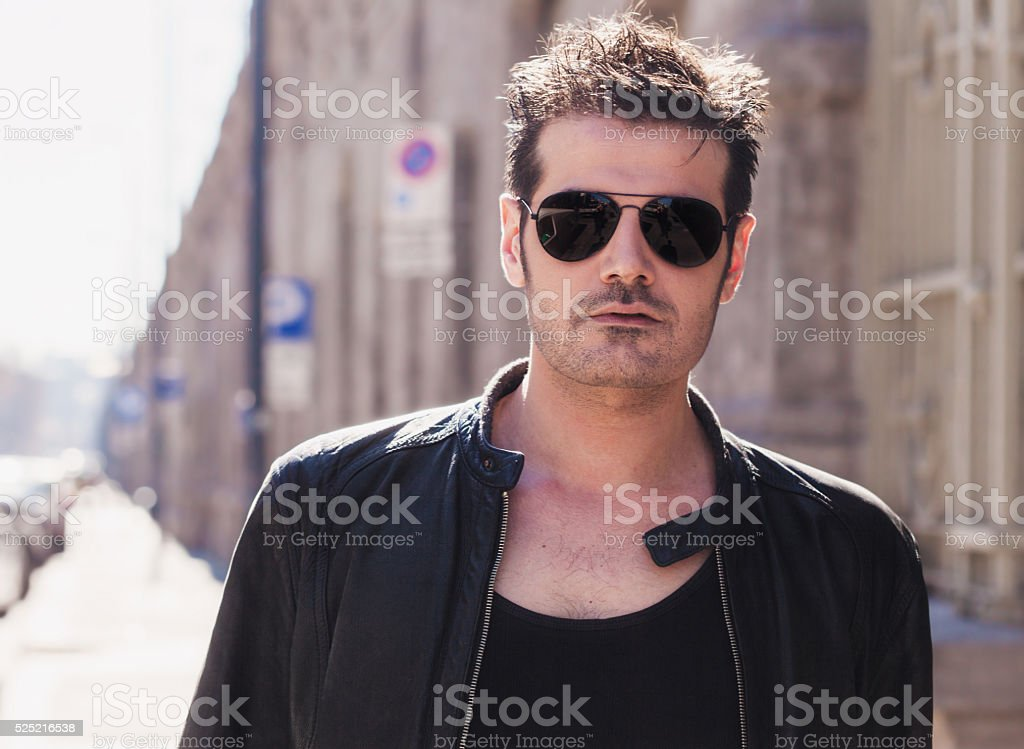 Handsome man portrait in the city wearing sunglasses stock photo