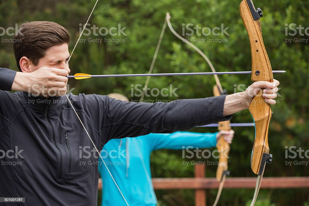 Handsome man practicing archery stock photo
