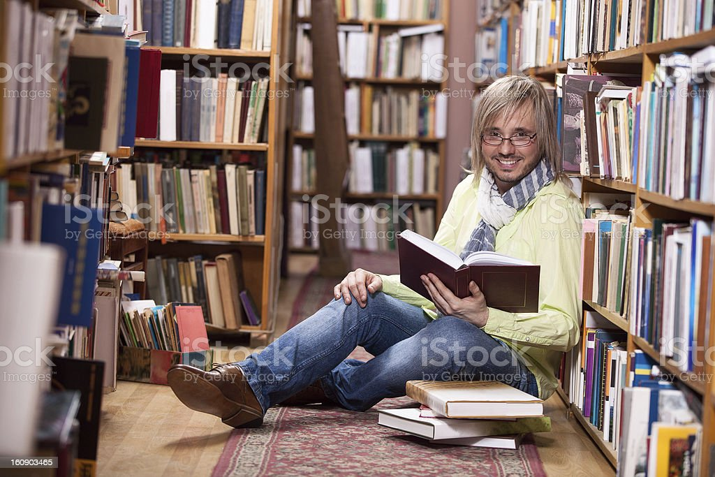 Handsome man reading book while sitting on floor in library royalty-free stock photo