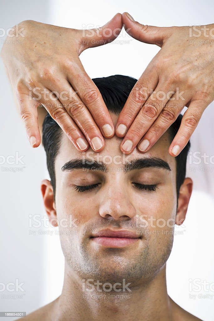 handsome man receives a head massage from a therapist stock photo