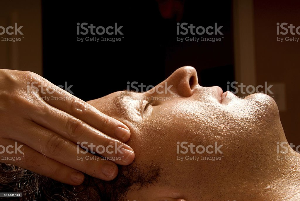 A handsome man receiving a facial massage royalty-free stock photo