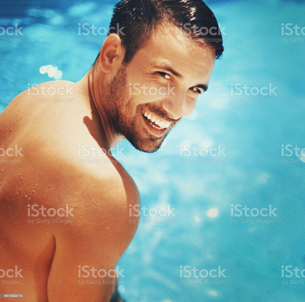 Handsome man relaxing by swimming pool. stock photo