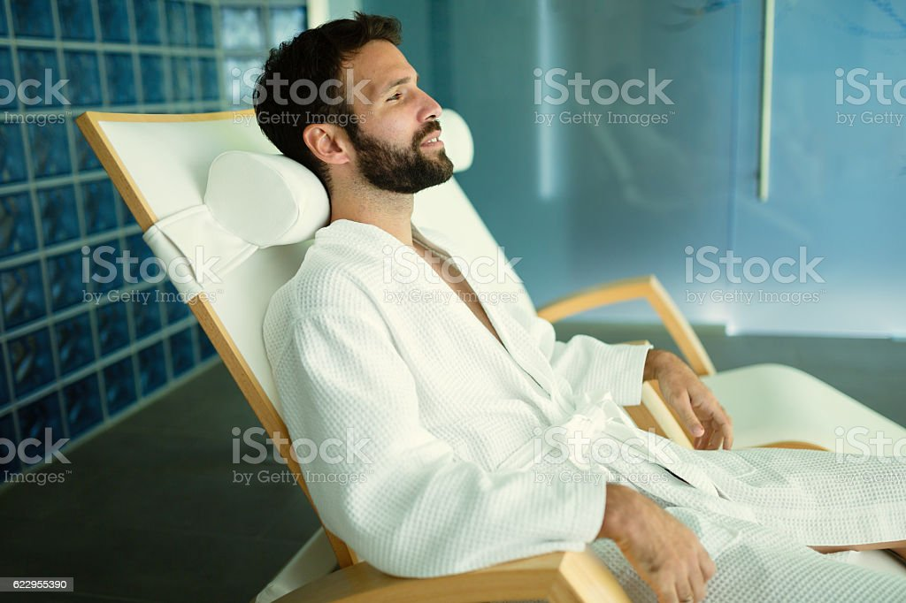 Handsome man relaxing in wellness center stock photo