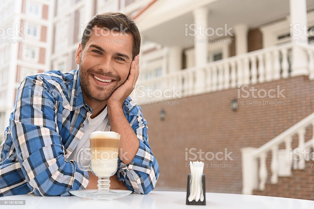 Handsome man relaxing with cup of latte stock photo