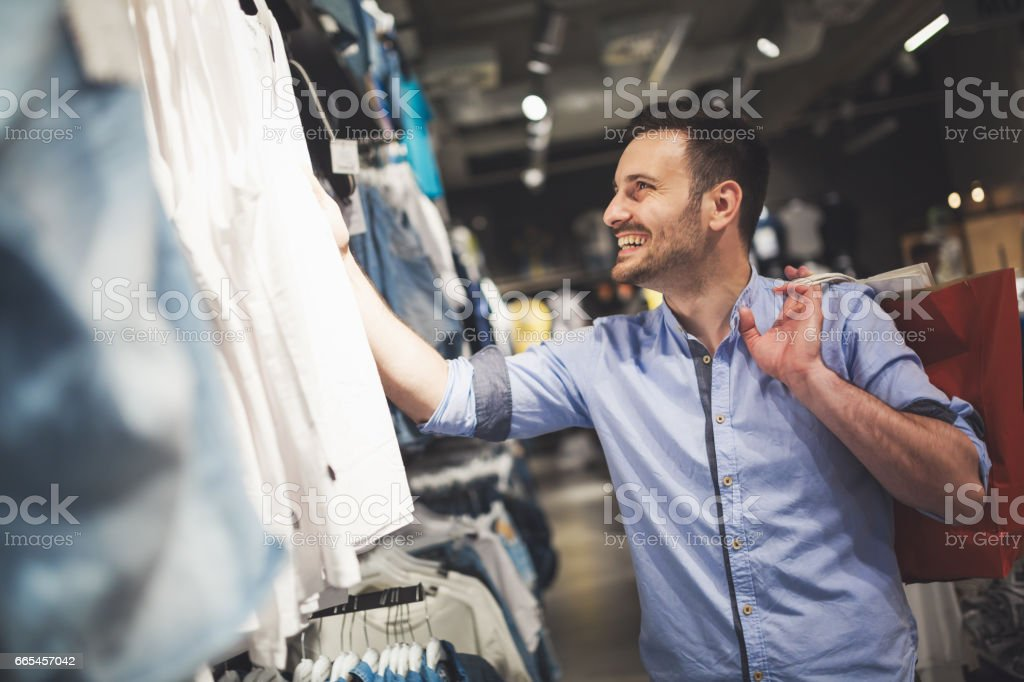 Handsome man shopping for new clothes in store stock photo