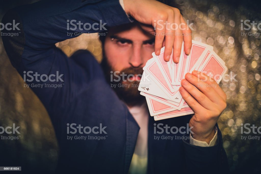 Handsome man showing cards trick stock photo
