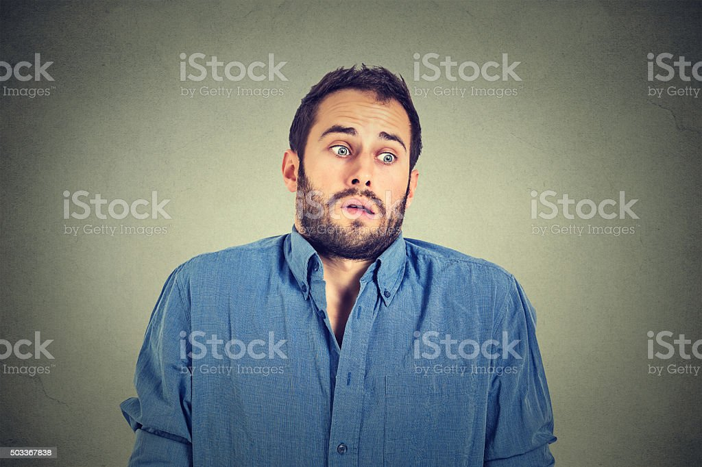 handsome man shrugging shoulders showing ignorance stock photo