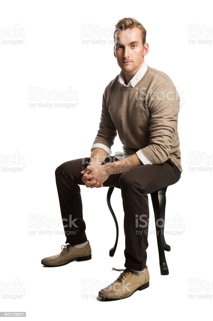 Handsome man sitting down indoors stock photo