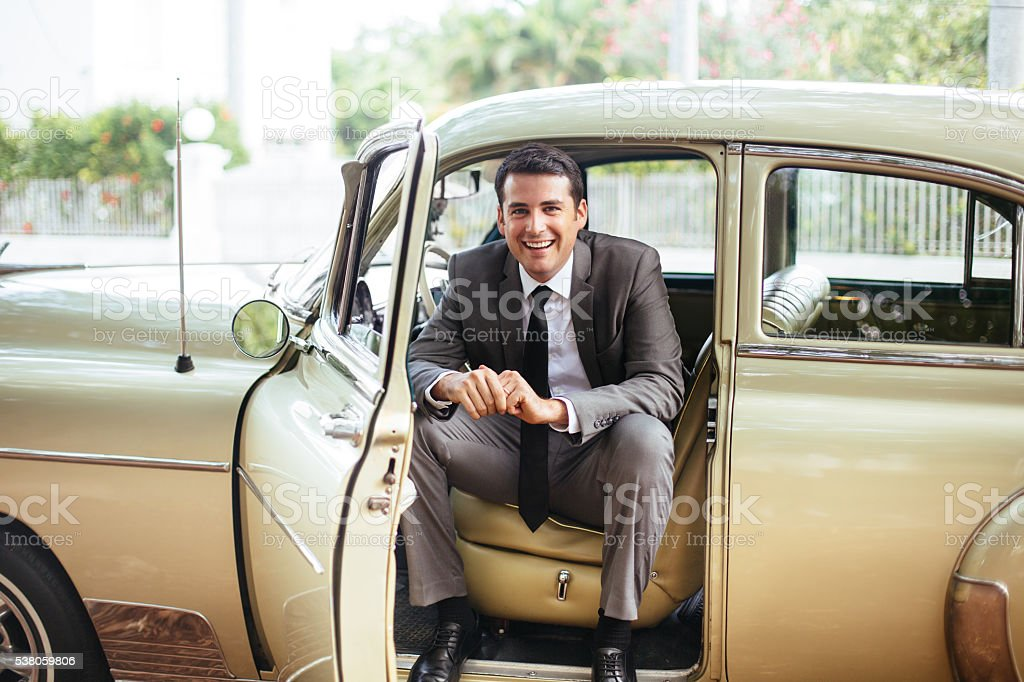Handsome man sitting in an old classic car stock photo