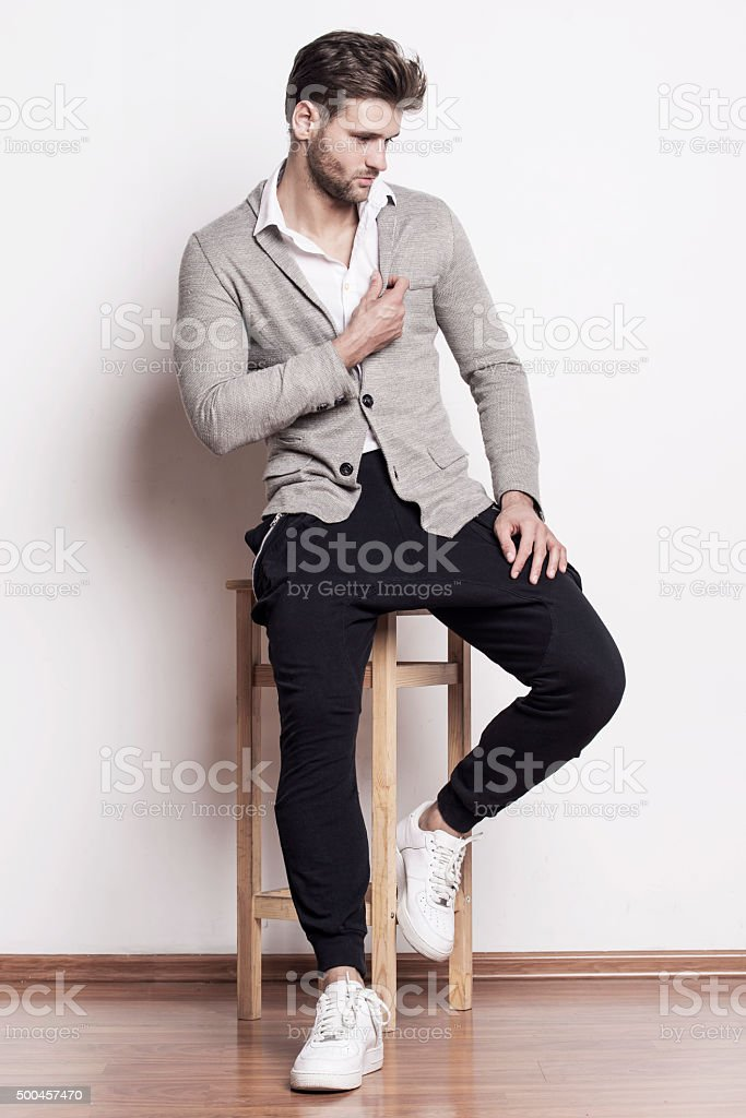 Handsome man sitting on a chair stock photo