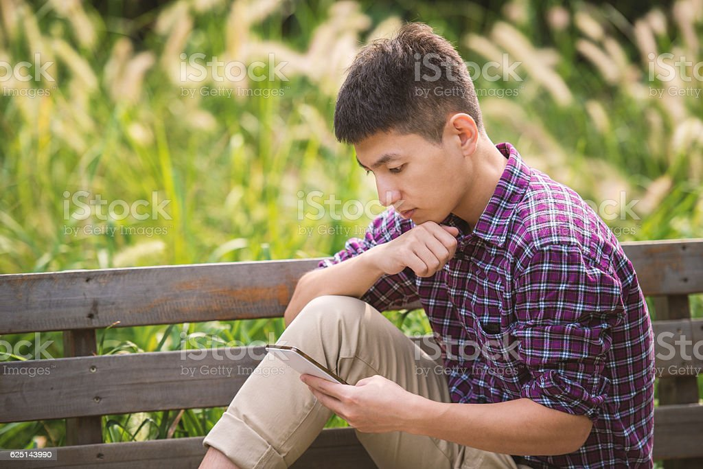 Handsome man sitting on bench and immersed in his smartphone stock photo