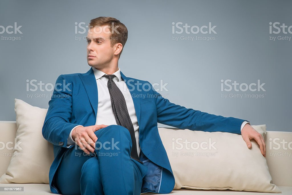 Handsome man sitting on the sofa stock photo