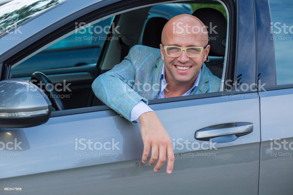 Handsome man smiling in his new car stock photo