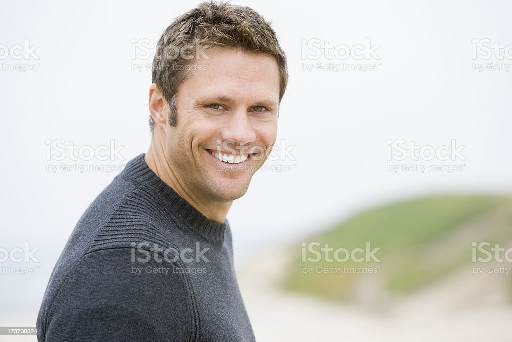 Handsome man smiling while standing on the beach royalty-free stock photo