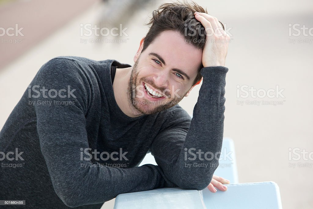 Handsome man smiling with hand in hair stock photo