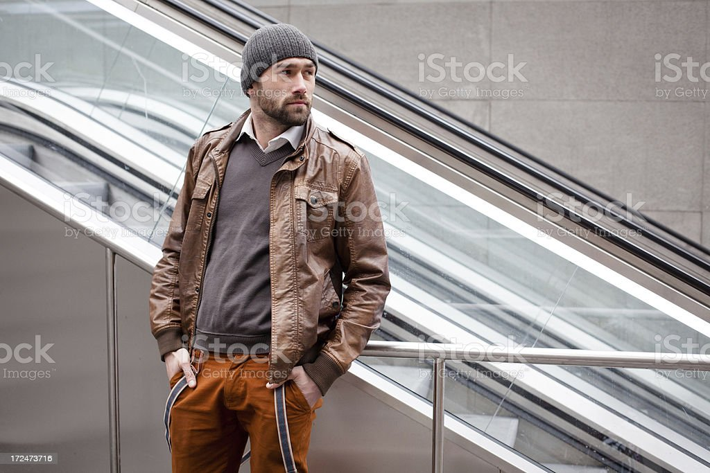 handsome man stands and waits in front of an escalator royalty-free stock photo