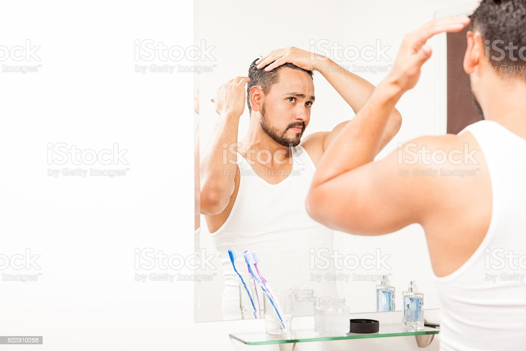Handsome man styling his hair with gel stock photo