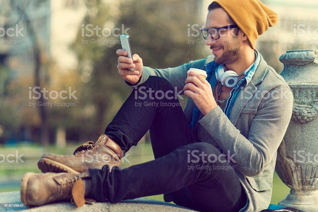 handsome man taking a break and using his smartphone stock photo
