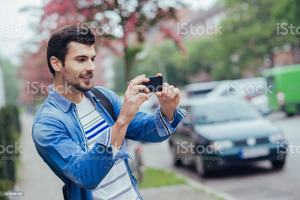 handsome man taking a photo with his phone stock photo