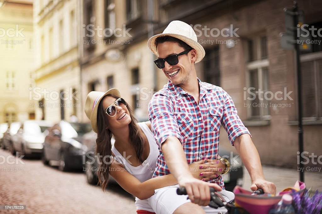 Handsome man taking his girlfriend on bicycle rack stock photo