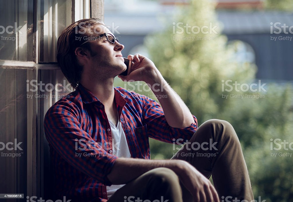 handsome man talking on his smartphone stock photo