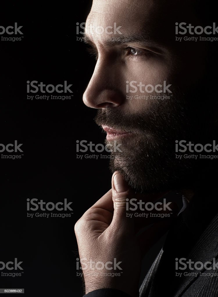 Handsome man touching his beard stock photo