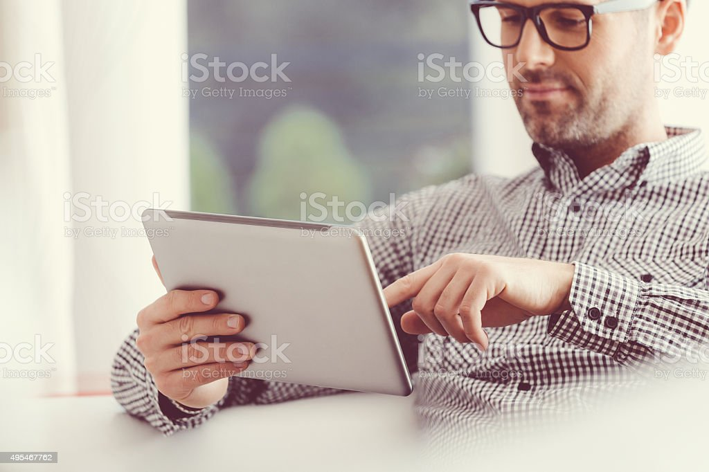 Handsome man using a digital tablet stock photo