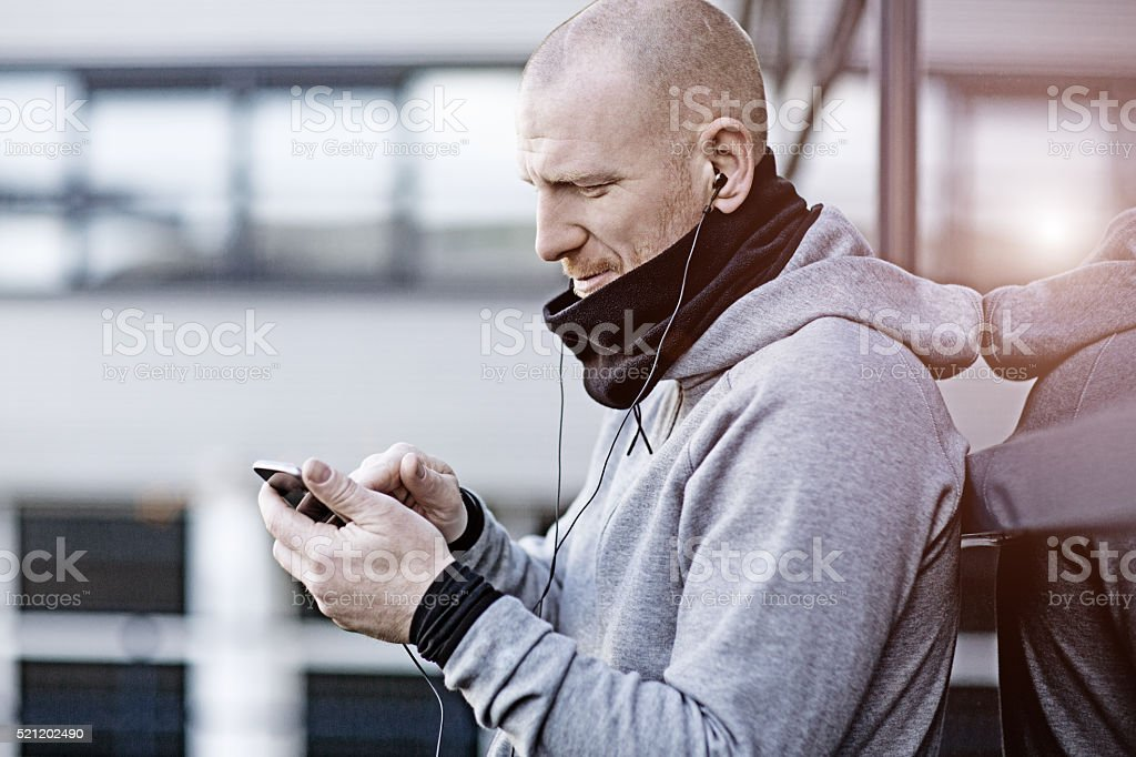 handsome man using his phone for jogging stock photo