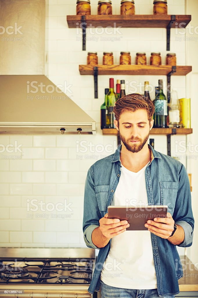 Handsome man using tablet computer in kitchen stock photo
