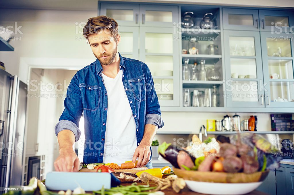 Handsome man using tablet computer while cooking in kitchen stock photo