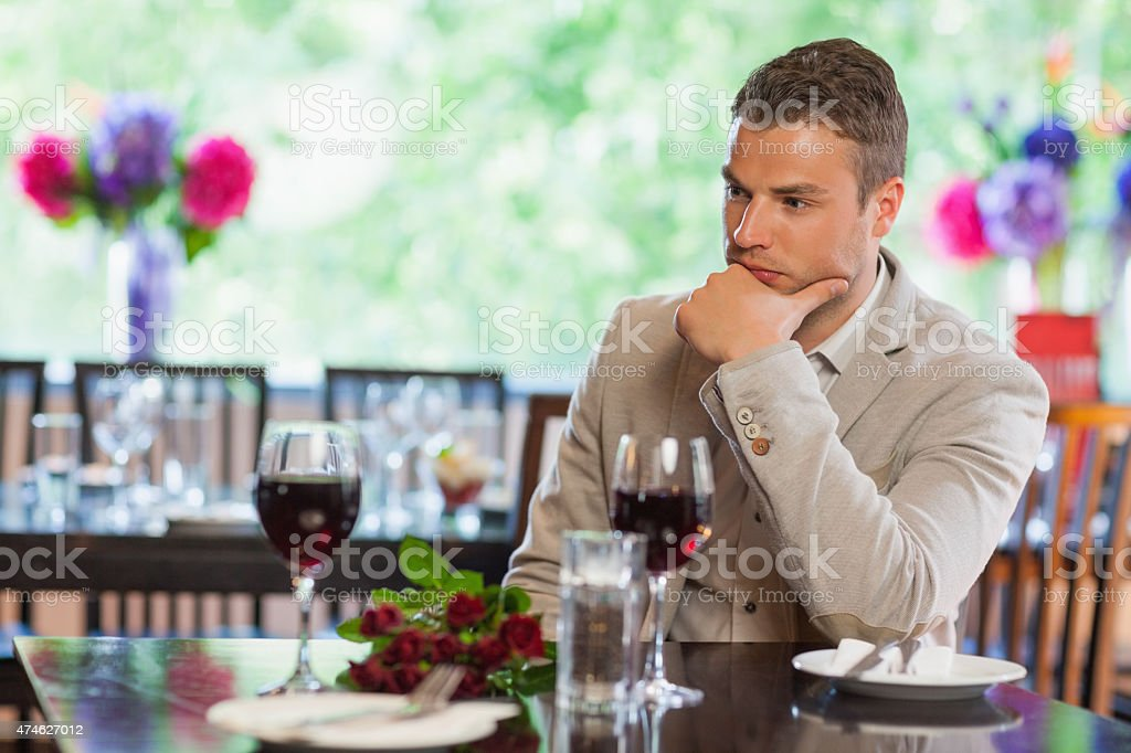 Handsome man waiting for his girlfriend at restaurant stock photo