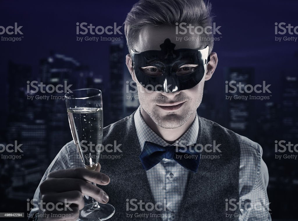Handsome man wearing carnival mask toasting with champagne stock photo