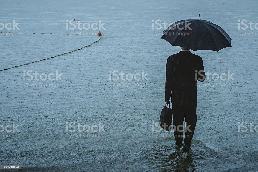 Handsome man wearing suit and holding umbrella during the rain stock photo