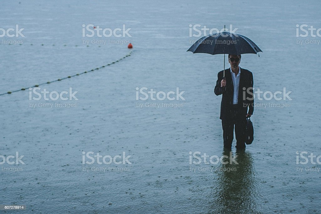 Handsome man wearing suit and holding umbrella stands in water stock photo